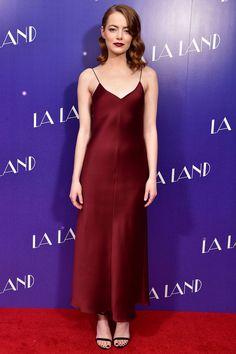 Emma Stone wearing a deep satin wine dress by The Row
