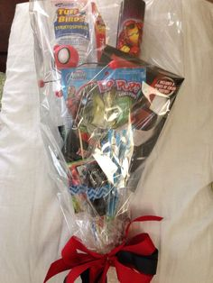 8 year old Boy's gift bouquet for hip hop dance recital. Attached items to bamboo skewers (.99 for 100 at Walmart) with hot glue and washi tape. Wrapped in cellophane and tied with a bow. Used rolled Avengers color book, pack of gum, hot wheels car, pixie sticks, balsa wood plane, spidey wall walker, pop rocks, slim Jim and slid an Ant Man book in there.