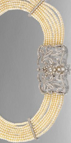 SEED PEARL AND DIAMOND COLLIER DE CHIEN, EARLY 20TH CENTURY Designed as eight rows of seed pearls connected by circular-cut diamond bars, centring on an open work plaque designed as foliate scrolls set with circular- and rose-cut diamonds, highlighted by a rose-cut diamond drop within a seed-pearl surround, length approximately 420mm.