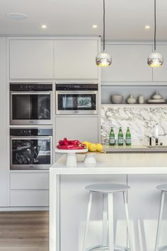 The kitchen is bright and open, featuring white cabinetry and an elegant island which doubles as a bar