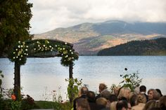 Frame the background of a lake wedding ceremony with a rustic wooden ceremony arch full of greenery. | Whiteface Club & Resort in Lake Placid, NY
