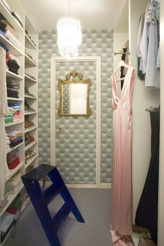 Chic gray tufted padded walk-in closet design with capiz chandelier, blue lucite closet ladder, gold leaf gilt ornate mirror and built-ins.