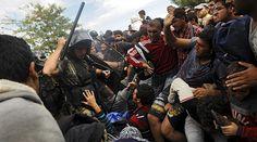 A Macedonian police officer raises his baton towards migrants to stop them from entering into Macedonia at Greece's border,near the village of Idomeni, Greece, August 22, 2015. © Alexandros Avramidis