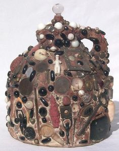 While memory jugs may look like junk, they are actually messages in a bottle.   This memory jug is built on an old molasses jug and is covered with an extraordinary assemblage including old buttons, an onyx mourning cross, shells, marbles, keys, a belt buckle, broach, stones, English coins, bottles, ceramic people, metallic objects,screws, chains, jewelry, a wishbone, and more. It is topped with a glass finial. It has a pencil eraser holder with a date of 1886