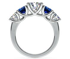 Two perfectly matched round sapphire gemstones paired with two perfectly matched round diamonds are prong set in this white gold gemstone engagement ring setting to accent your choice of center diamond. Proudly made in the USA.