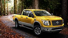 2016 Nissan Titan PRO-4X® pickup truck side view shown driving in the woods in Solar Flare
