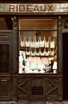 paris-1966- there's a certain charm in all of the  blush toned underpinnings hung en masse in the window in contrast to the industrial building... great photo