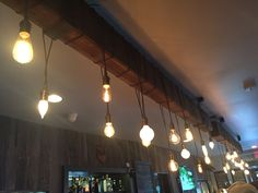 Bar lighting at Bowman's North. Reclaimed wood suspended from ceiling with iron brackets and bolts. Single strand of lights, plugged into a flush mount ceiling port, different styles of bulbs.
