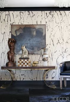 A snakeskin-and-brass console in the hallway outside the master bedroom; the wall is covered in a hand-painted Porter Teleo wallpaper. - Kelly Wearstler Design - Midcentury Modern Interiors
