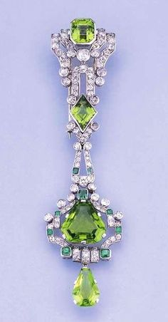 AN ART DECO PERIDOT, EMERALD AND DIAMOND BROOCH/PENDANT Designed as a clip brooch and detachable pendant, the four vari-cut peridots within openwork old-cut diamond and emerald geometric surround, circa 1925, 10.9 cm. high