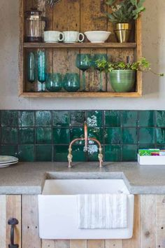 Get the look: Upcycled green tiles were used to create the vivid tile border in the kitchen. The work surface was handmade by pouring and polishing concrete. The sink is a reclaimed Belfast sink, fitted with taps custom made from copper pipes.