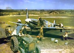 Groundsmen refuel a Supermarine Spitfire Mk Vb ZD-Z of No 222 Squadron RAF, from a tractor-towed petrol browser, while amourers replenish it's .303 machine guns - North Weald, Essex, England - World War 2