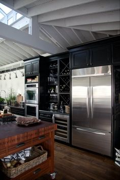 Yes please, exactly this. Dark beautiful cabinetry. Awesome wine rack built into the wall, gorgeous stainless steel appliances. And a rustic, dark wood island. I. Want. All of it.