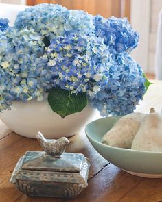 Treasured collectibles pair with a lush arrangement of beautiful blue hydrangeas for a charming tabletop vignette. #southernladymag #hydrangeas #vignette #vignettestyling #beautifulhomes #southernhomes #interiordesign #designinspo #southernhome #tabletopinspo
