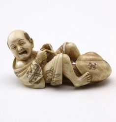 """Netsuke in the form of a man with a snail Place of origin Japan  Period Meiji period 1868 - 1912 → Japan Year 19th century Media category Sculpture Materials used carved ivory Dimensions 2.7 x 5.8 cm  Signature & date Signed base, in Japanese, red ink, incised """"Seiko [or Shizutora]"""". Not dated. Credit Bequest of Henry Albert Nathan 1941"""