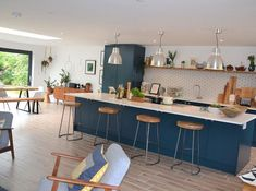 Open plan kitchen living dining room. Industrial vibe with blue kitchen and scaffolding plank shelves