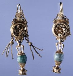 Pair of gold ear-rings. Although missing some of their pendants, these earrings are intricately made, with careful attention to detail. They follow the common disc and amphora type of the middle and late Hellenistic period, but the use of a large emerald is unusual: emeralds became more popular during the Roman period. Hellenistic 2tn BC