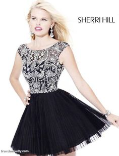 Sherri Hill 2814  Feel like a ballerina in this stunning cocktail mini by Sherri Hill. Gorgeous rhinestones cover the bodice of this elegant style adding an extra touch of flair for your special night. Sheer illusion fabric is elegantly embellished along the bust and cap sleeves, and the deep back plunges to a V ending just above natural waist. The accordion crinkle skirt has a slight tutu effect as layers of crinoline add extra volume to this fun and flirty style.