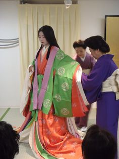 A woman being dressed in junihitoe layer by layer at a kimono demonstration.