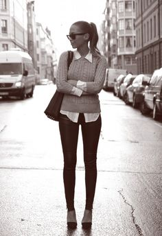 City girl in black skinny jeans, knit sweater, and collared skirt looking pretty chic.