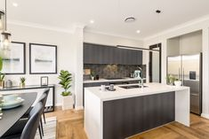 The mix of light and dark, juxtaposing the cabinets and splashback with the Fresh Concrete Caesarstone waterfall benchtops, is an attractive centerpiece for this open plan living hub. Pictured is the Tulloch 25 home design built for the Build for a Cure 2017 project. #mcdonaldjones #mcdonaldjoneshomes #BuildForACure