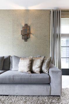 """De muur is behangen met behang met goud. De bank is van Interiors DMF. Accessoires geven sfeer aan een interieur. De kussentjes in verschillende materialen zorgen voor een speels effect. De vloer is een dubbel gerookte eiken parket in visgraat gelegd. Foto: Anneke Gambon – """"Stijlvol Wonen"""" - © Sanoma Regional Belgium N.V."""