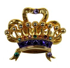 "Plated crown with a bow design. Decorated with purple, green & gold crystals. Size 2"" length X 2"" width"