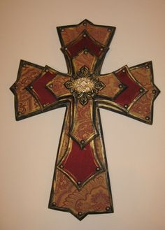 Fabric covered cross with gold and rhinestone brooch in center