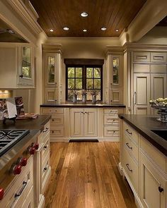 Love the design of this kitchen. Wood floors and ceiling with light fixtures. Color Scheme of Cabinetry and counters!