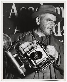 Weegee the Famous and his Speed Graphic camera, standing in front of a sign for the Academy Awards.  Unidentified Photographer, Los Angeles