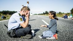 Danish policeman charms the world while playing with a refugee child on the Danish highway.