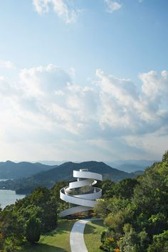 Two curving staircases encircle the exterior of this wedding chapel by Tokyo-based architect Hiroshi Nakamura, meeting at a rooftop platform that overlooks the Hiroshima coastline