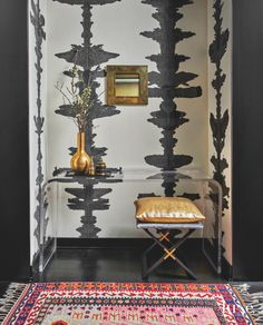 Porter Teleo's hand-painted inkblot wallcovering from David Sutherland and a colorful vintage Turkish kilim rug by Djoharian from 1stdibs create a dramatic first impression in the entry foyer. The acrylic Waterfall console is by New York-based Aaron R. Thomas, and the stool is from Atelier Gary Lee. The antique brass mosaic mirror is from Pavilion Antiques