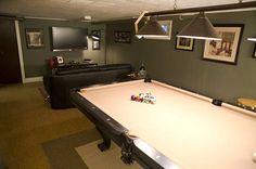 This man cave features a pool table and prime seating for watching the game, as well as a wet bar for watching the games in style