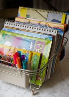 Here's a clever idea to help you keep your kids' art supplies organized. Buy a small dish drainer (either metal or plastic will do), stack coloring books and tablets of watercolor paper where the plates would normally go, and use the silverware bins to store pencils, crayons and markers. What could be easier?