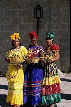 SuperStock - Portrait of three young women in traditional clothing holding baskets of flowers, Havana, Cuba