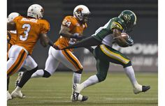 B.C. Lions cornerback Byron Parker holds onto Edmonton Eskimos running back Hugh Charles' (R) jersey as he runs down field in the first half of their CFL game in Vancouver.