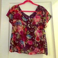 """Beautiful floral sheer top. Size M Navy and colorful floral print top (sheer) on the shorter side but not super cropped. I'm 5""""4 and it only shows teeny amount of belly when I lift my hands. (Reaches hips about) Unique detail with cutouts in the back. One of a kind top i had to cutout the tag because it was showing through the back but this is Romeo and Juliet Couture brand and a size M. Anyone from a small to even a smaller large could fit in this comfortably. Love this top only wore it…"""