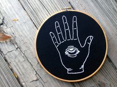 Evil Eye. This 8 inch embroidery hoop features white thread on a black fabric. All Thread Honey hoop art is handmade by me with lots of love and care. If you would like this embroidery (or any other) in a different color, size, fabric etc., just let me know (no extra charge)! Custom orders are always welcome. This hoop is MADE TO ORDER. Each hoop is handmade by me, and because of that please allow 1-2 weeks for creation. If you need the hoop sooner than that, just message me and we can w...