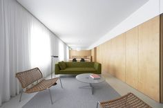 Apartment Refurbishment In Pamplona by Inigo Beguiristain - Living Loft.  Wood paneling and a full wall curtain.
