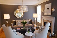 The dark walls in this living room are lightened up with white trim, furniture and accents. The silver in the mirror, sconces, vases, and lamps is sprinkled ...