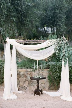 Green leaves accent a wooden arbor draped with cream fabric to create a backdrop…