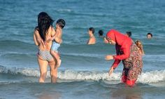"""Nice Becomes Latest French City to Impose Burkini Ban,"" The Guardian (19 August 2016). The French Riviera city was the scene of last month's truck attack on Bastille Day revellers that left 86 people dead. Fifteen resorts in the south-east and others elsewhere in France have already banned the burkini, including the nearby city of Cannes. Photo: A woman wears a burkini on a beach in Tunisia. Photograph: Fethi Belaid/AFP/Getty Images."