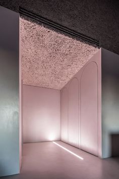 Apartment in Rome by Antonino Cardillo where roughly textured plaster creates lumpy brown surfaces across the upper walls and ceilings.