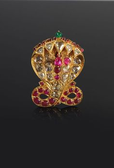 A fine gold Sarpech (24k) or ''Aigrette'' depicting a large King Cobra, set with nineteen diamonds, twelve cabochon rubies (two of them pendants), and one emerald, using the Kundan method. The fixation on the back, which was probably originally enamelled, is made using several pins to attach the jewel onto a turban. The motif on the front is Indian which was fashioned in the first half of the 19th Century, the shell on the back having been made using European techniques in India c…