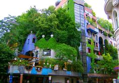 The incredible Hundertwasserhaus by Austrian artist-cum-architect Friedensreich Hundertwasser is an apartment complex covered with trees and foliage.
