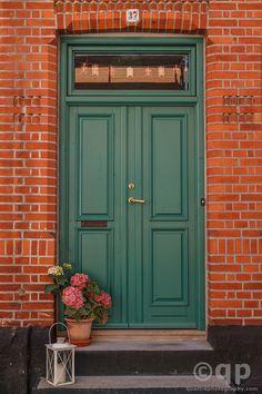 green door, red brick exterior
