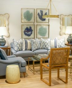 A medley of blues mix beautifully in this vignette featuring a pair of extraordinarily comfortable chairs and matching sofa with English arms. Four framed blue sea fans hang on the wall while a pair of Bunny Williams pheasant feather lamps flank each side of the sofa. #hivepalmbeach #shophive #shoplocal #homedecor #seafans #palmbeach #livingroom #bunnywilliams #lamps