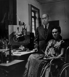 Dr.Juan Farill in Casa Azul studio, 1951, Gisele Freund. Kahlo poses in a wheelchair, with palette and brushes, with Farill who performed her seven spinal operations the year before. In the painting next to them, she uses a heart as a palette, her blood as paint. It was her last signed self-portrait. She died in 1954 at age 47.