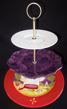 """Three Tier Stand, Jewelry Stand, Vanity Stand, Cake Plate, Tray, Mismatched Plates, Cupcake Stand, Dessert, Appetizer, Tidbit, Vintage, Antique, Tuscan. Vintage three tiered plate stand. Made with antique and vintage plates and new stand hardware. Top plate is 6.5"""", the Middle plate is 9"""", and the bottom plate in 11.5"""". Total tray height when assembled is 13"""" to the top of the handle. This is a handmade, one of a kind item! I buy the vintage plates at estate sales so there may be some…"""